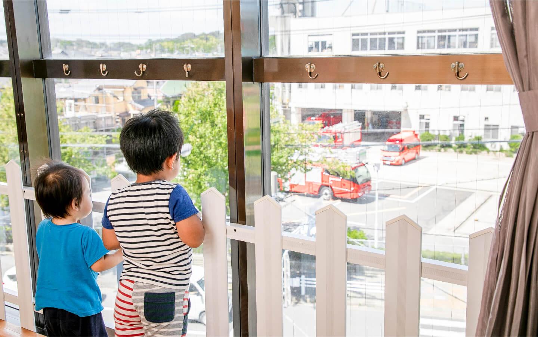 窓から消防車をみる子供2人